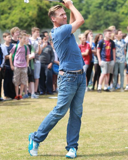 Ian Poulter plays a shot, on his return to his old school
