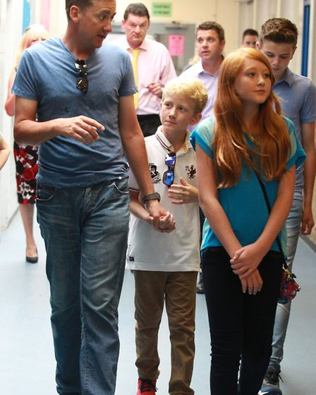 Ian Poulter walks with his children, Luke and Aimee-Leigh during the tour of Barclay school, Stevena
