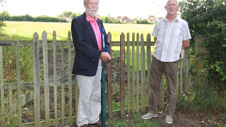 Cllr Barry Livesey and Cllr Terry Cobb stand by the entrance of the field where the development is p