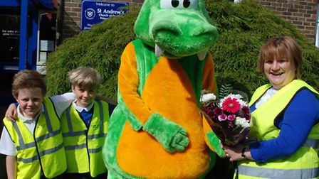 Claire with Buster the dinosaur and pupils at the school