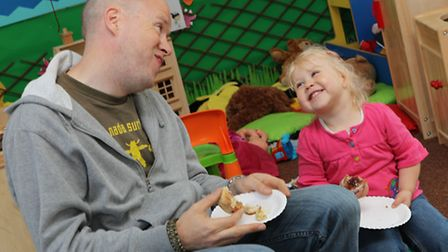 A father and daughter enjoy some cakes at the Strathmore Macmillan coffee morning