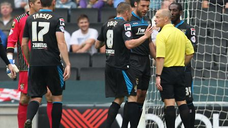 Stevenage players, including Jon Ashton, protest to referee Andy Woolmer about the awarding off a pe