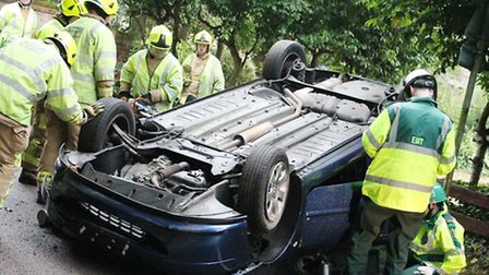 Firefighters and paramedics speak to the woman trapped in her overturned car. Credit: East of Englan