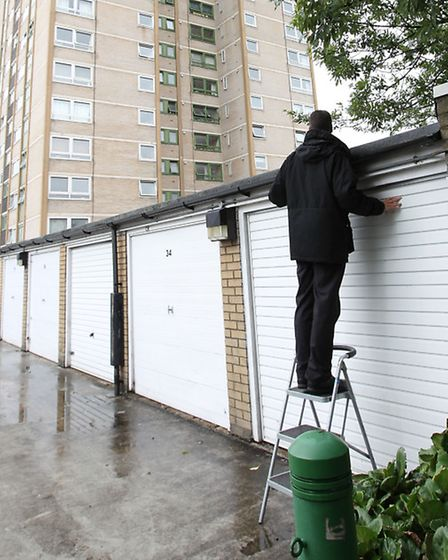 A member of the police search team searches the garages outside Harrow Court