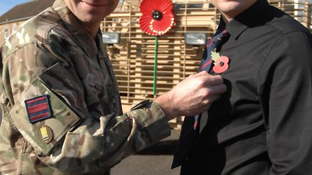 Lt Col Eldon Millar presents the first poppy of the campaign to Sam Jack.