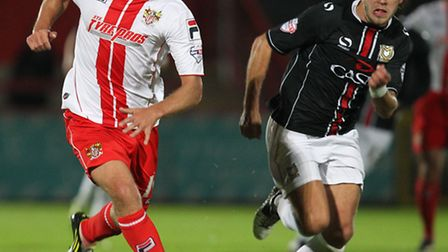 Simon Heslop chases the ball with Alan Smith. Photo: Harry Hubbard