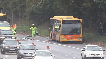 The bendy bus sits on the hard shoulder as traffic enforcement officers clear up diesel spillage in