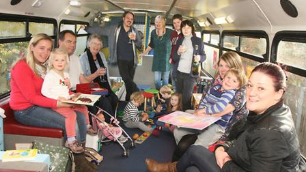 Parents, grand parents, children, and Buffy bus staff in the bus celebrate the Big Lottery funding a