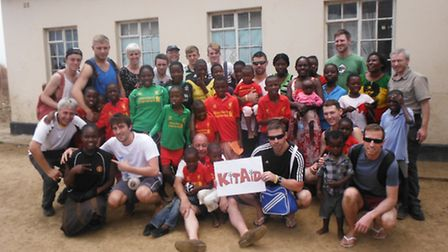Members of FC Cornerstone with orphans wearing donated Liverpool FC kits