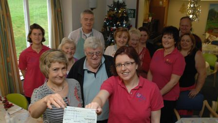 Julia Pointer (left), manager of The Garden Room, receives a £500 cheque from Claire Jennings, chair