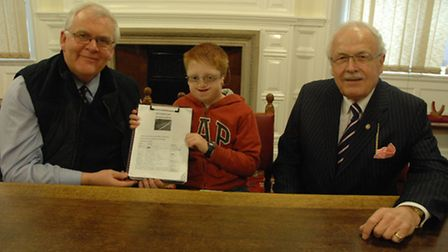 Max hands his petition over to town clerk Simon Lloyd and Cllr Alastair Walters, chairman of the Utt