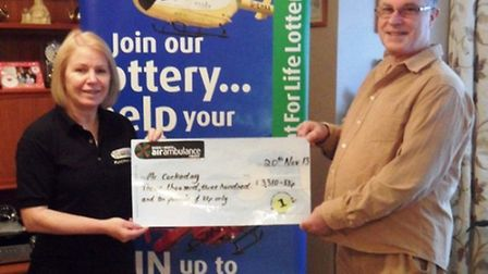 Janice Flower, Flight for Life Lottery manager, presents Glyn Cockaday with his winning cheque.