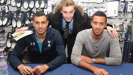 Nacer Chadli and Mousa Dembele pose for a photograph with Spurs fan Liam Power
