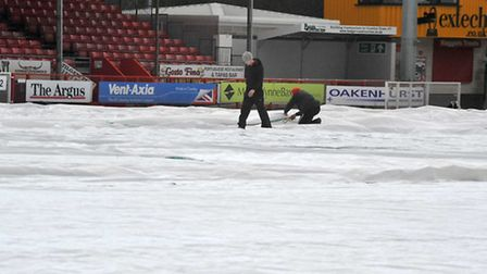 Crawley Town's groundsmen working after the game was called off. Photo: Alan Millard