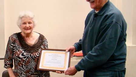 SWCS president Sean Brady presents Betty Clarke with a framed certificate in honour of her 60 years'