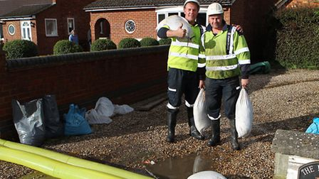 Ringway workers JJ Davies and Jason Grimes help lay sandbags across residents driveways in Little Wy