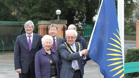 Chairman of Uttlesford District Council, Cllr Eric Hicks, is seen raising the flag to celebrate Comm