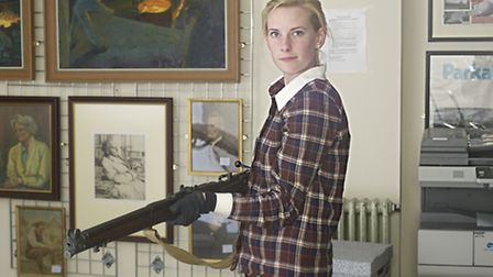 Collections officer Aimee Flack with a rifle used by the Letchworth Garden City Home Guard during Wo