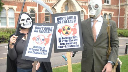 Protesters in a Grim Reaper outfit and gas masks outside Uttlesford District Council.