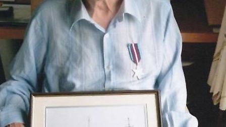 Eric Atkins wearing his Arctic Star and holding a photograph of HMS Westcott - the ship he worked on