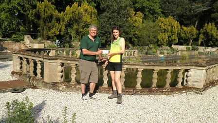 Chloe Searle hands over a cheque to Gardens of Easton Lodge trustee Angus Drever at the historic ven