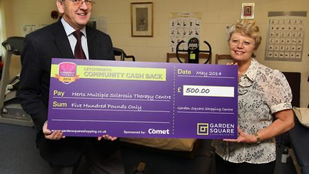 Garden Square Shopping Centre manager Paul Haynes presents a cheque for £500 to Hertfordshire MS The