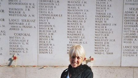 Author Jean Handley holding her father Cyril Payne's war medals during a visit to the Menin Gate in