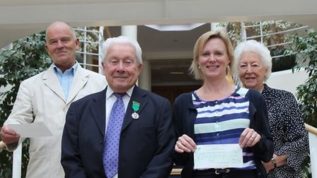 Ian Barnard (left) and Sarah Calder (second from right) receive cheques from Cllr Eric Hicks and his