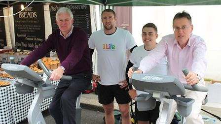 UDC councillors Howard Rolfe and Simon Howell test their legs on the bike, overseen by Dan Booker an