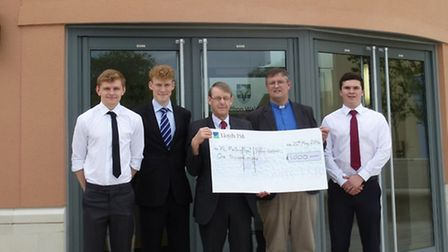 A Level Leisure Studies students Josh Jones, George Peasgood and Jack Skellam present a cheque for £
