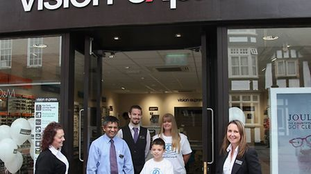 Kyle cuts the ribbon to open Vision Express in Hitchin watched by mum Mellissa