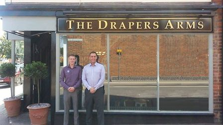 Manager Andy Cottam stands outside the newly-opened Drapers Arms with a member of staff
