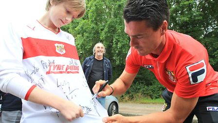 Ronnie Henry signs a young fan's shirt