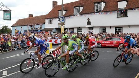 The Peleton tackles the sharp left hand turn in front of the 450th year old original School Room of