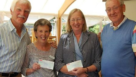 Michael Homfray-Cooper, left, seniors section caption, presents the proceeds of charity day to repre
