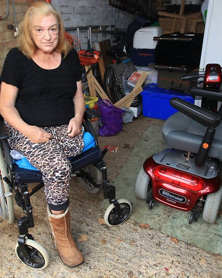 Yvette Summerton next to her mobility scooter which became stuck in a muddy underpass