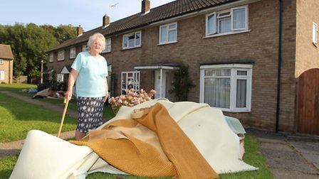 Dorothy Melhuish outside her house with the carpet damaged by the flood