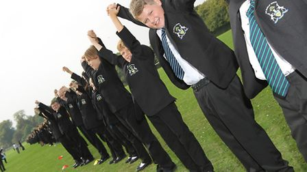 Barclays students join hands in a line across the field to celebrate their coming together with Almo