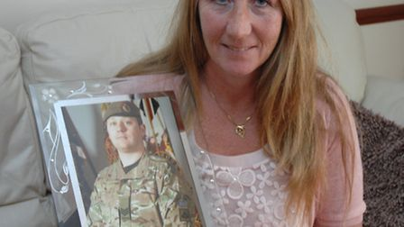 Elaine Freeman, who is on trial for attempted murder, with a picture of her son, Nigel, who was kill
