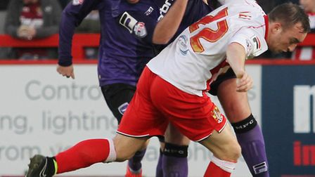 Charlie Lee tussles with a defender in the match against Morecambe. Photo: Danny Loo