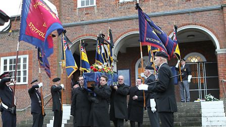 Standard bearers form a guard of honour as Ray Cole's coffin is carried to the hearse