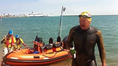 Andy Nation celebrates with a bottle of champagne after reaching Dover during his swimming challenge