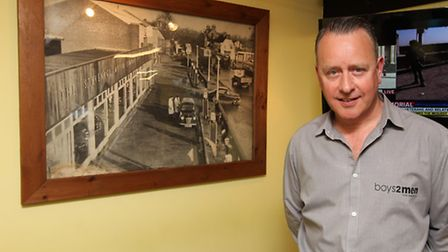 Boys 2 Men owner Craig Chalkwright in front of one of the pictures showing his shop in the 1950's