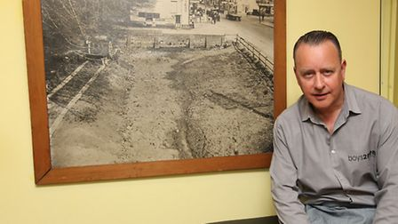 Boys 2 Men owner Craig Chalkwright in front of a picture showing the filling in of a pond in the 193