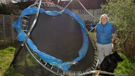 Peter Horner with his dog Sam and the trampoline which was carried by the wind to his garden