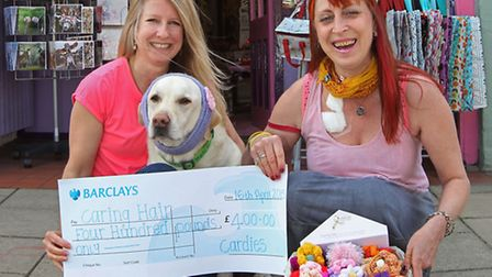 Cardies owner Jo Sorrell and her dog jack present a cheque to Lucy Macnab for Jo Gates and cancer ha