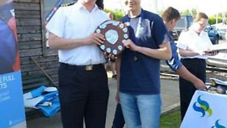 Cadet Joe Smith receiving the Area Windsurf Shied from the Eastern Area sea cadet officer, commander
