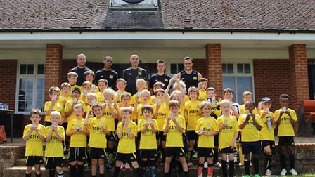 Youngsters from Active Soccer with their trophies in front of the pavilion at Hitchin Boys School. P