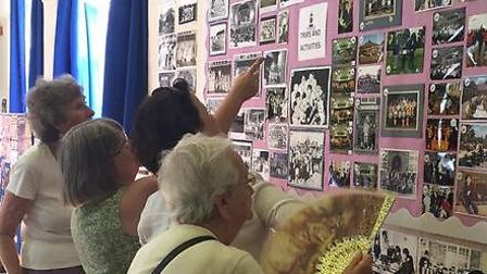 Former pupils look at old photos during the reunion at Wilshere Dacre Junior Academy.