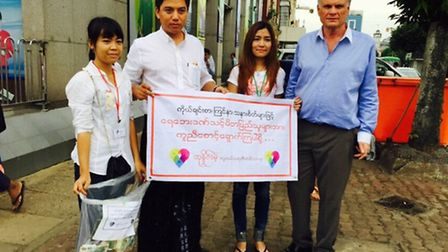 Laurie Clayden (r) with Burmese aid volunteers on Tuesday in Yangon the sign they are holding reads
